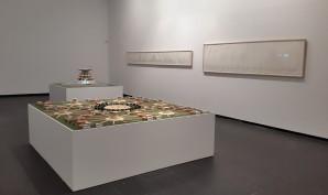 Carlos Garaicoa, Campus o la Babel del conocimiento, 2002-2004 Instalación. Dos Maquetas de madera de balsa, acrílico, cartulina, barro, luz eléctrica: Una maqueta 85 x 155 x 155 cm. Una maqueta 20,32 x 207,5 x 205.2 cm. Dos dibujos a lápiz tinta en papel: Un dibujo 61.46 x 259.58 cm. Un dibujo 33.02 x 360.68 cm. Texto en vinilo sobre pared, dos monitores con animaciones en 3D transferidas a DVDs Dimensiones variables